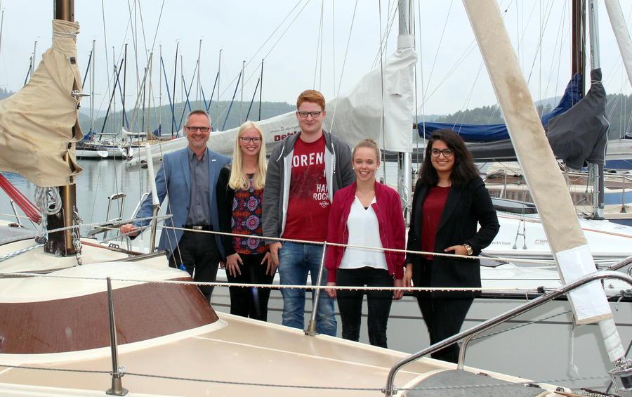 Fünf Menschen auf einem Bootssteg hinter einem Boot