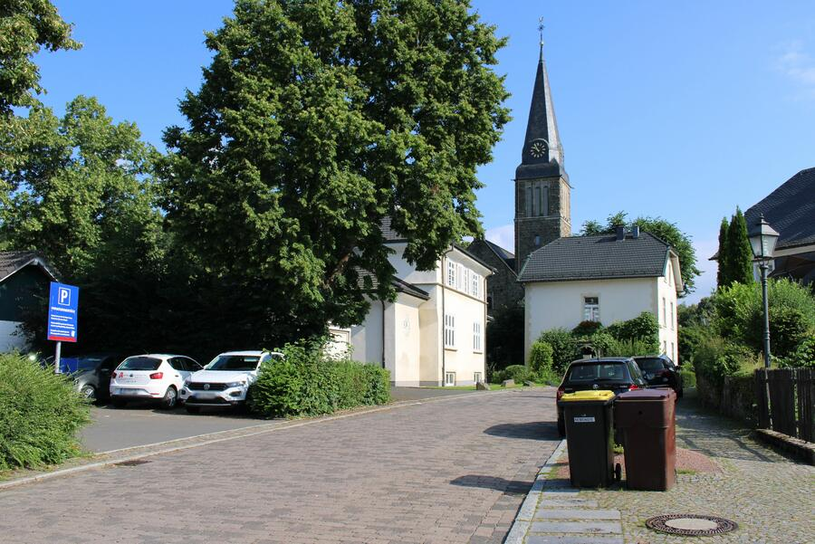 Bild vergrößern: Eine Straße mit einem Kirchturm im Hintergrund