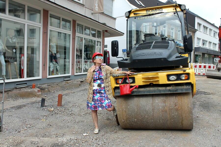 Bild vergrößern: Eine bunt gekleidete Frau an einer Baustellen-Walze