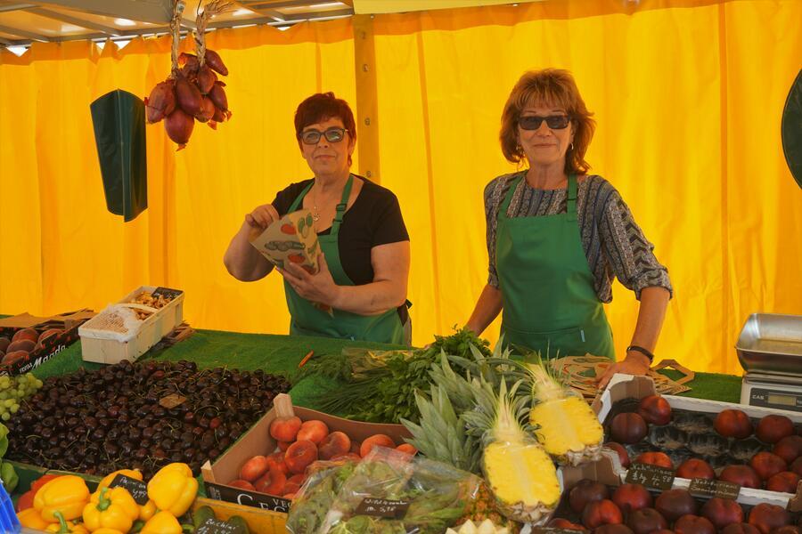Bild vergrößern: Zwei Markthändlerinnen hinter einem Obst- und Gemüsestand.